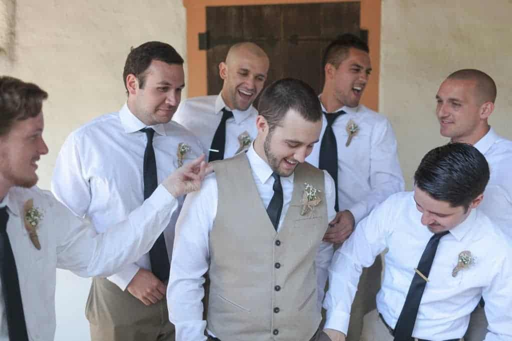 a groom in a white dress shirt, tan vest, and black tie with 6 groomsmen all in white dress shirts and black ties, seemingly laughing and joking around together
