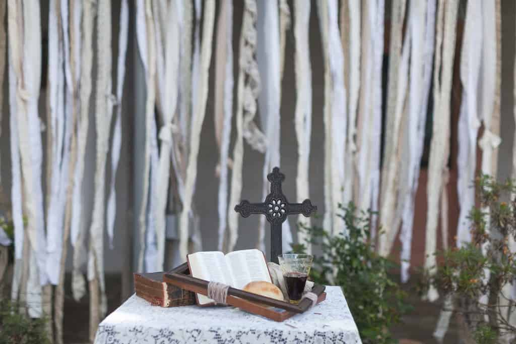a small table set for a wedding ceremony, with a cross, wine, bread, and a bible on it