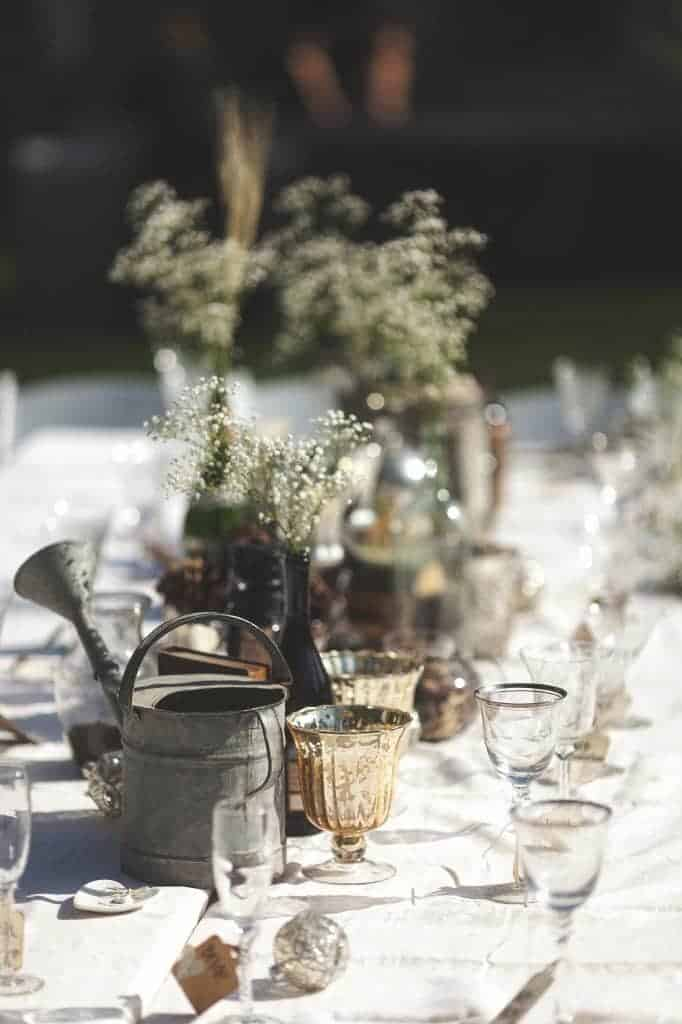 close up of the rustic centerpieces of a wedding dining table, with items including a metal watering can, small vases, and gold goblets