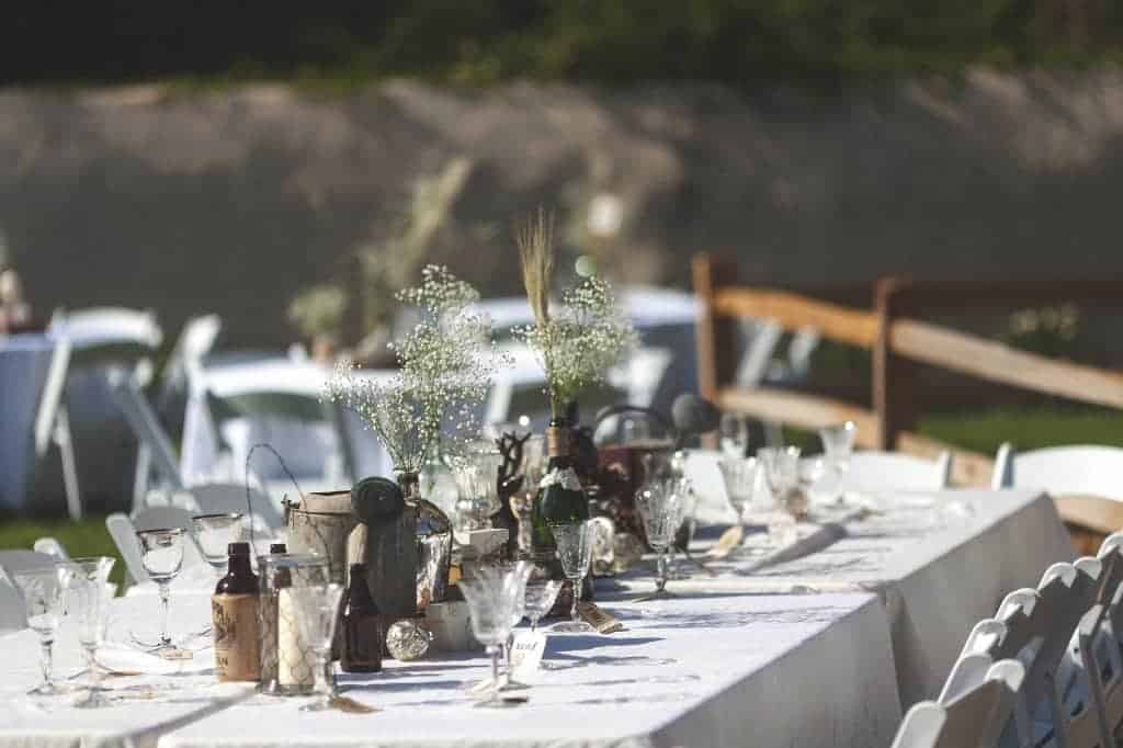 a table with a white tablecloth and place settings for a wedding reception with rustic centerpieces including bottles, jars, baby's breath, wheat, and wooden accent pieces