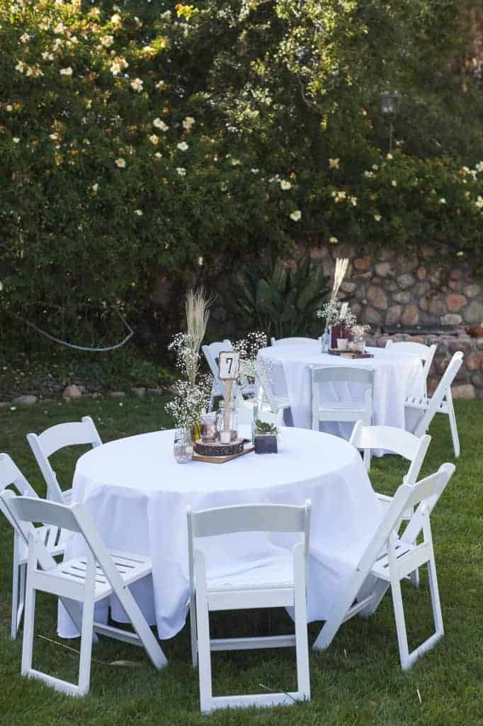 two round tables with white tablecloths, each with rustic style centerpieces and table numbers. both tables have white folding chairs around them