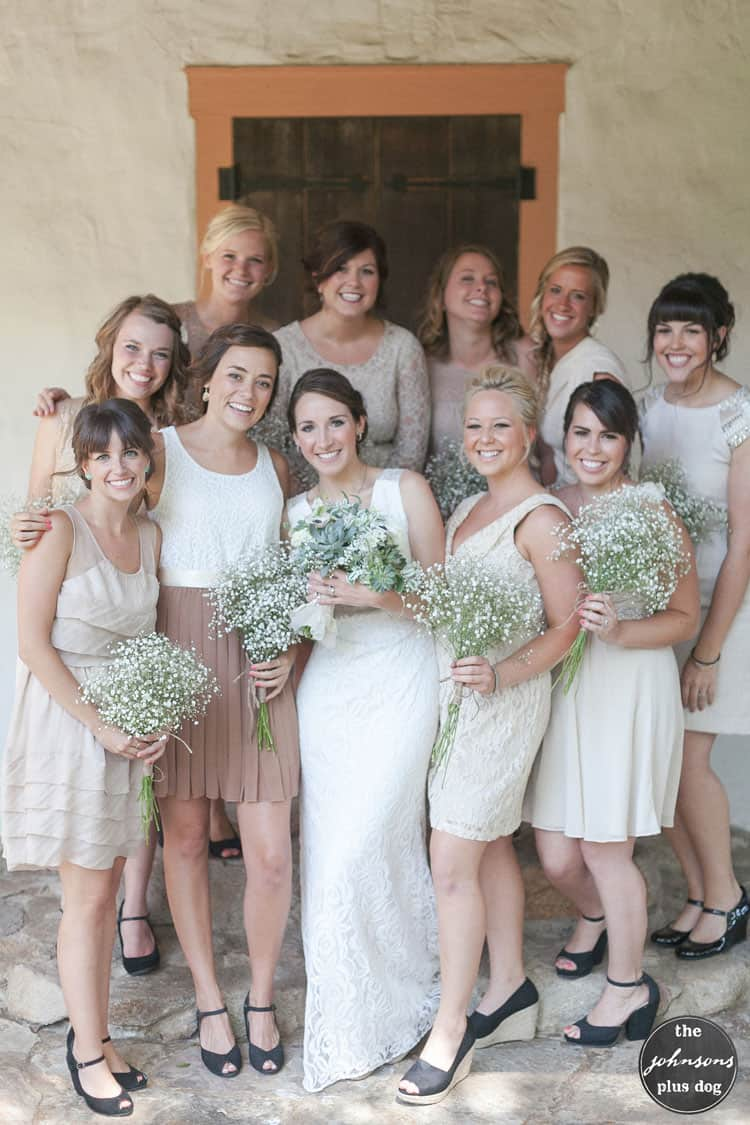 a bride in a white wedding dress holding a greenery bouquet, and her ten bridesmaids wearing various dresses in shades of tan and light brown, each holding a bouquet of baby's breath