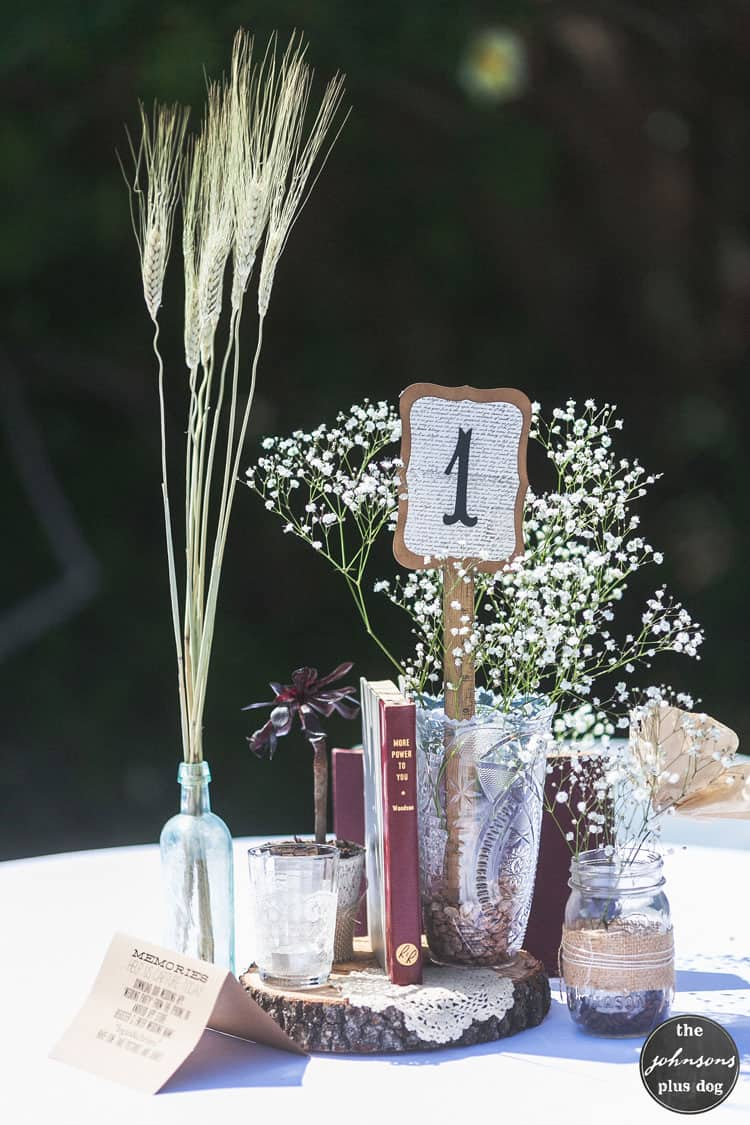 a simple table centerpiece decoration with wheat in a glass bottle vase, baby's breath in a larger vase, a book, a jar, a thin slice of a log, and the table number one.
