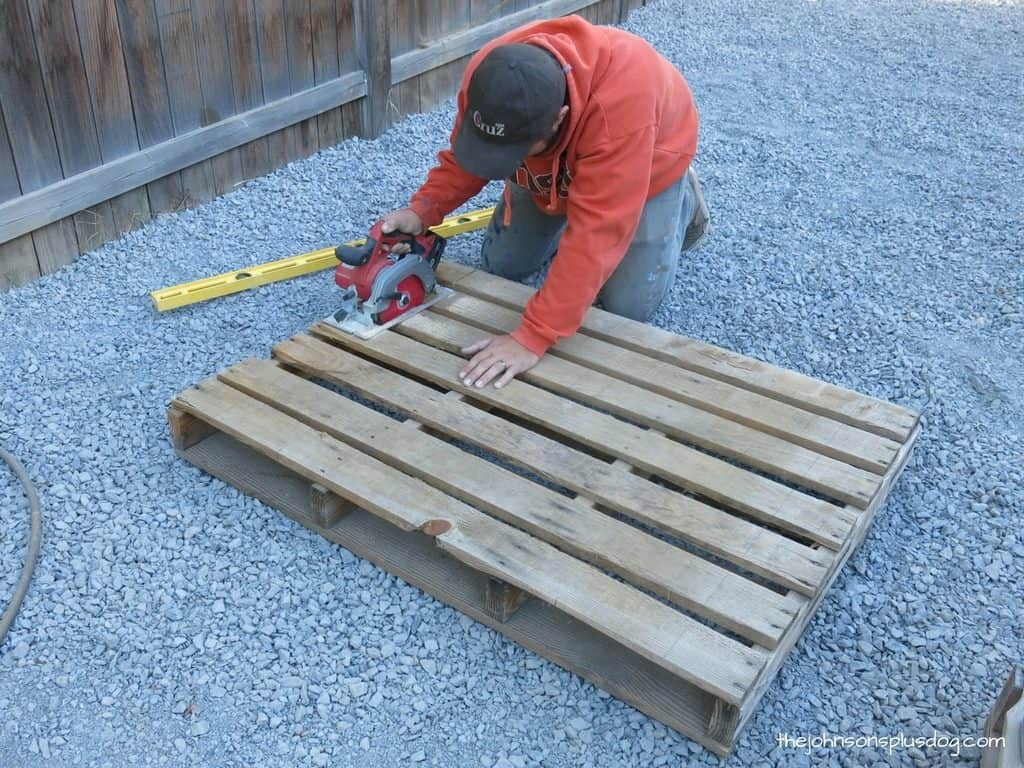 man cutting a wooden pallet with a circular saw