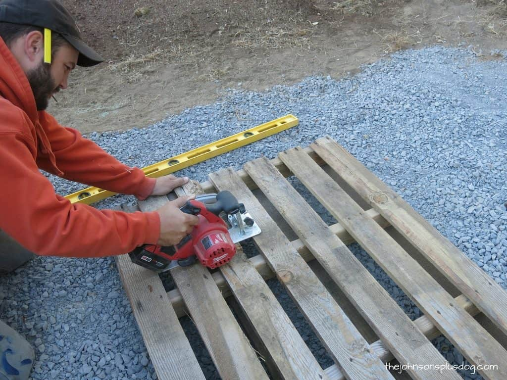 man cutting a wooden pallet down to size using a circular saw