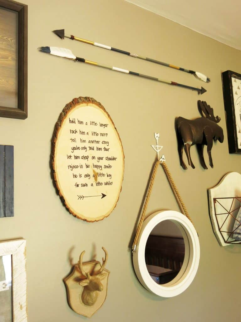 rustic woodland art pieces hung on a wall, including a metal moose, two arrows, a wooden deer head, a small mirror, and a round wooden slab with a poem
