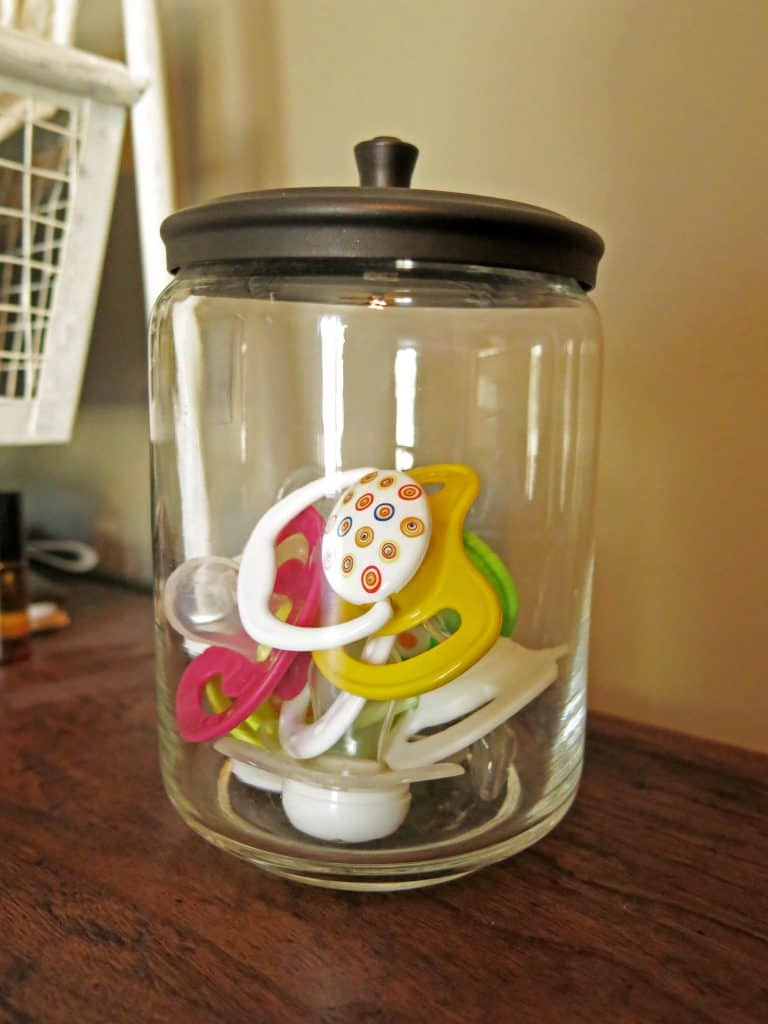 pacifiers in a glass jar with a lid