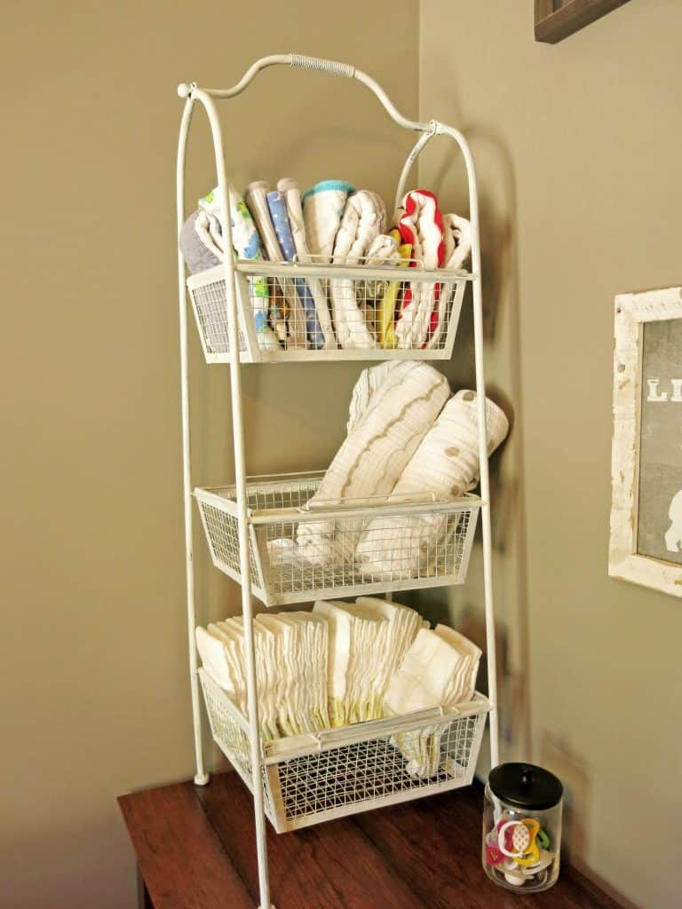 a 3 shelf storage area for a baby changing station