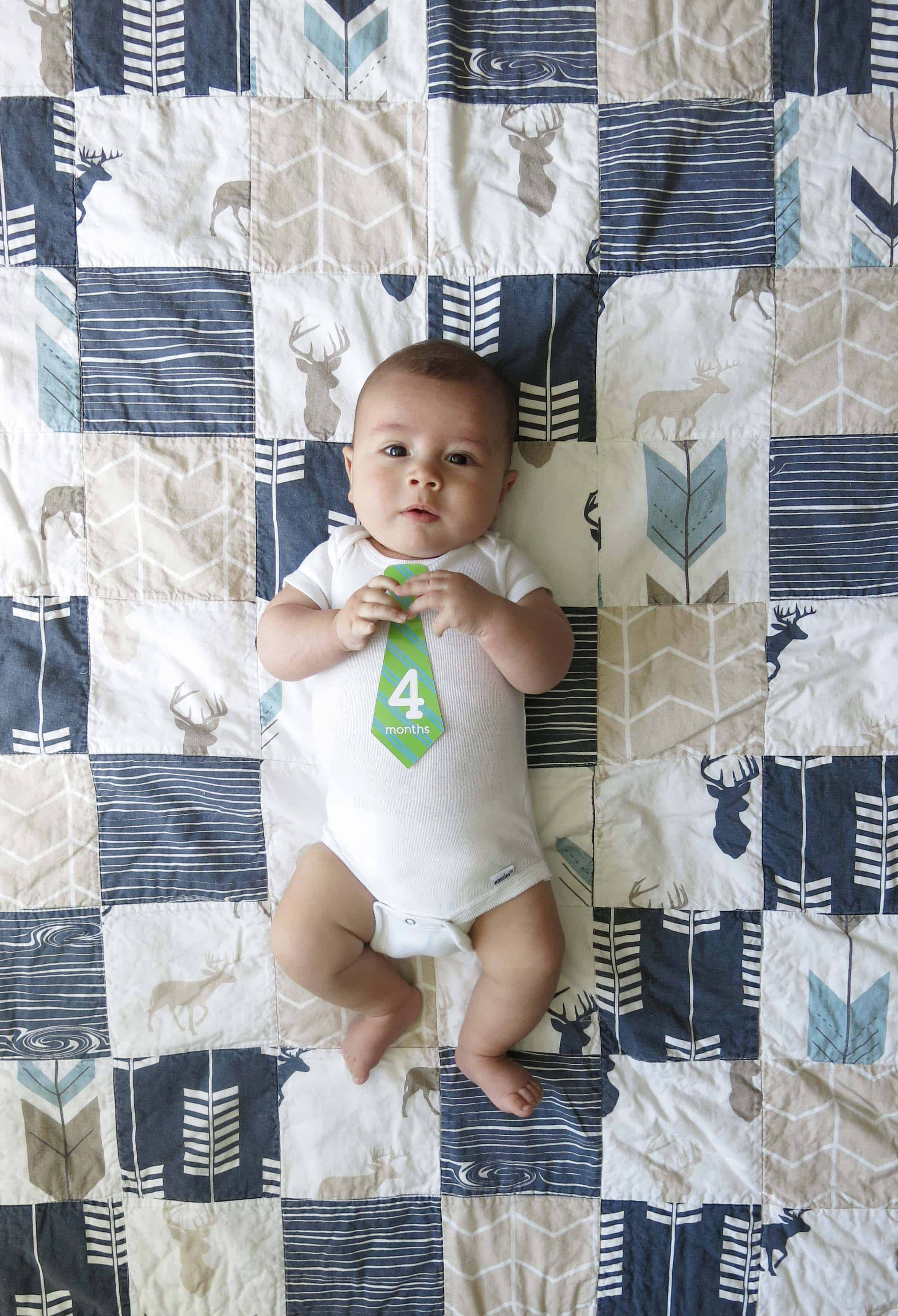 a baby with a tie that says 4 months, laying on a rustic woodland themed blanket