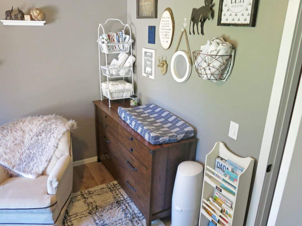 a view of a changing table in the corner of a home nursery with rustic decor