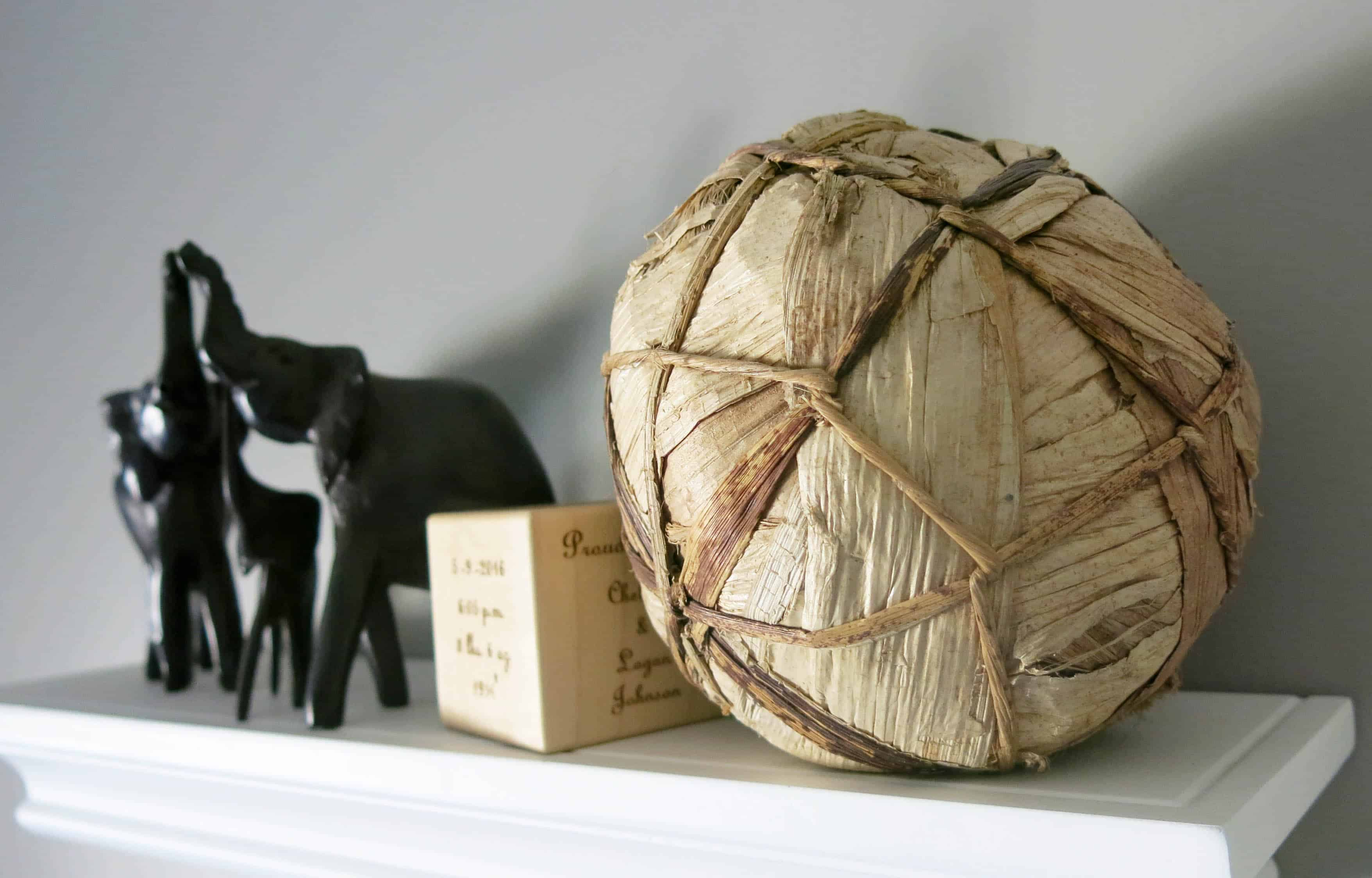 black elephant trinkets, a wooden box, and a rope and corn husk decorative ball on a white shelf
