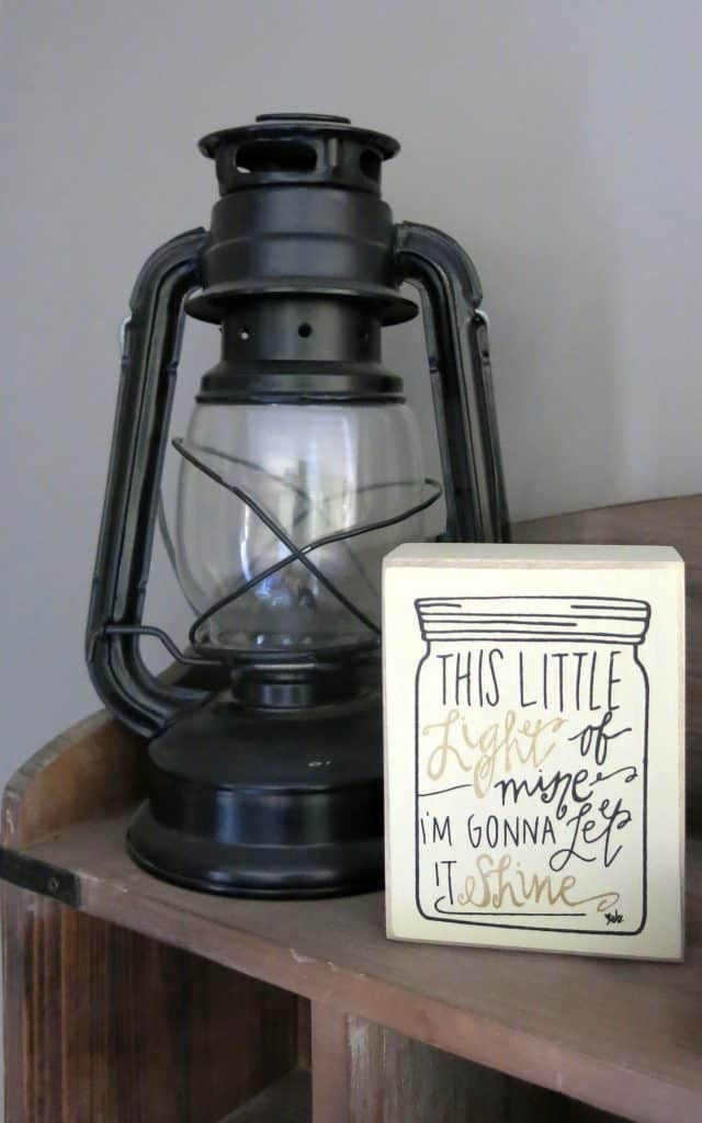 "black metal camping lantern and a small sign that reads ""this little light of mine, I'm gonna let it shine"""