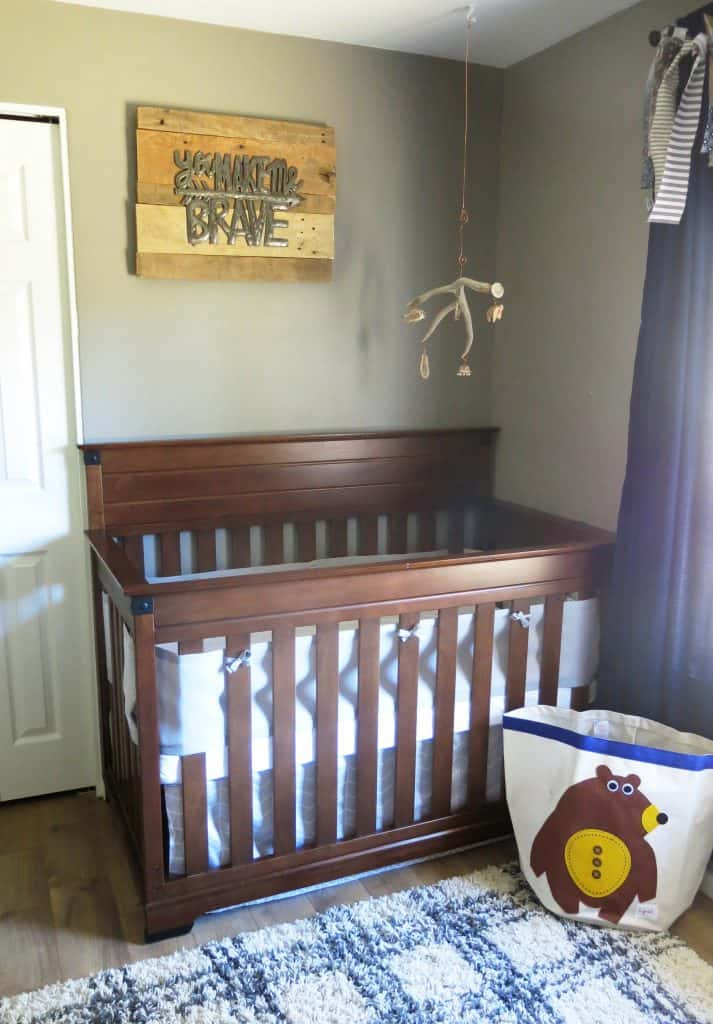 "a wooden crib with a metal sign above it that says ""you make me brave,"" and an antler mobile hanging above the crib"