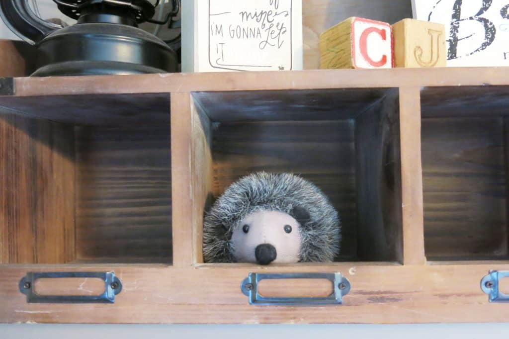 close up of a stuffed hedgehog toy on a wooden shelf in a woodland nursery