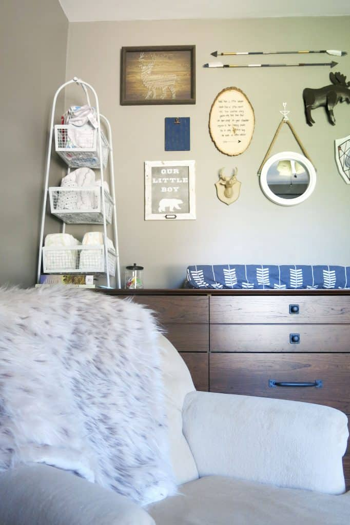 a nursery with a faux fur throw over a chair, a dresser used as changing table, and a gallery wall over the dresser