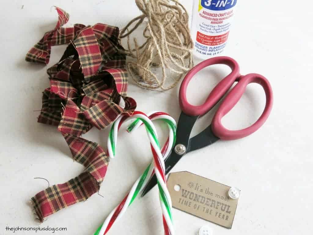 supplies laid out on a white surface, supplies are two plastic candy canes, long strips of fabric, twine, craft glue, scissors, and a decorative tag