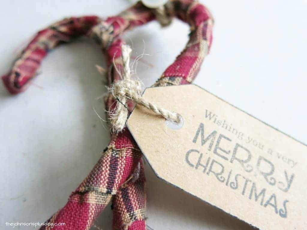 close up of twine tied around two fabric candy canes, also holding on a decorative tag that says wishing you a very merry christmas