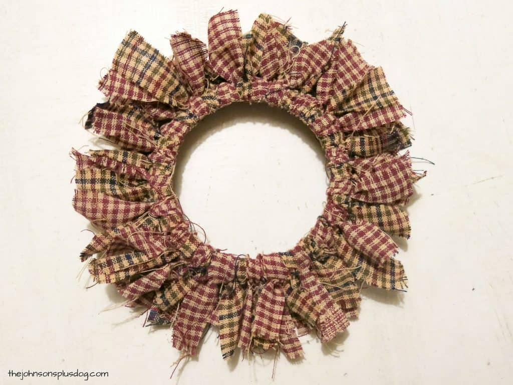 a fabric wreath, with a center ring and decorative frayed edges