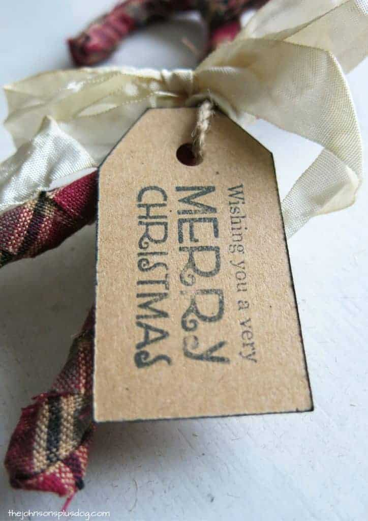close up of the decorative tag on finished fabric christmas ornaments, it says wishing you a very merry christmas on it
