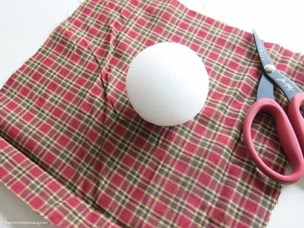 a styrofoam ball sitting on a square of plaid fabric with scissors next to it