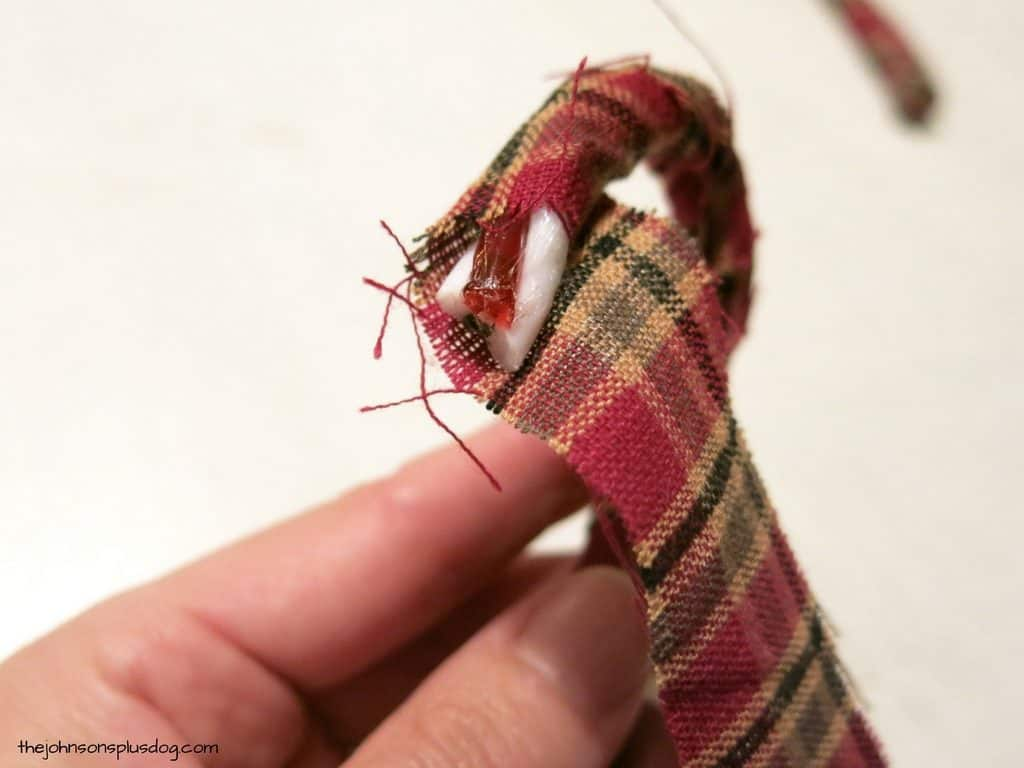 plaid fabric wrapped in a spiral all the way up a plastic candy cane, leaving only the tip exposed