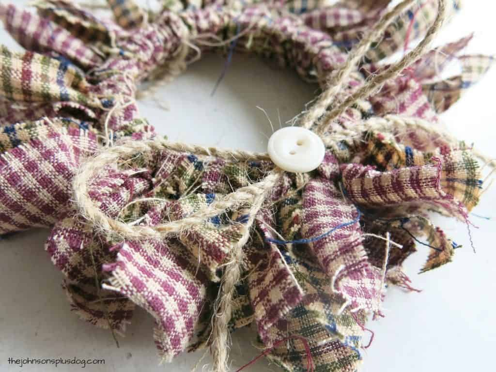 close up of a twine bow with a button on the front, attached to the wreath ornament