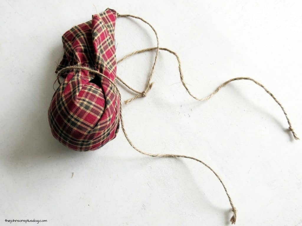 a ball covered loosely in fabric with twine loosely wrapped around the extra fabric