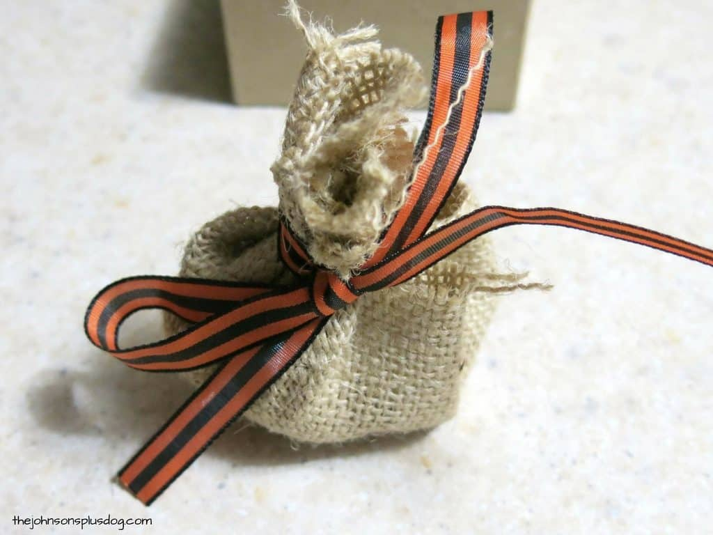 Small burlap sack tied with festival black and orange ribbon for a fall pregnancy announcement