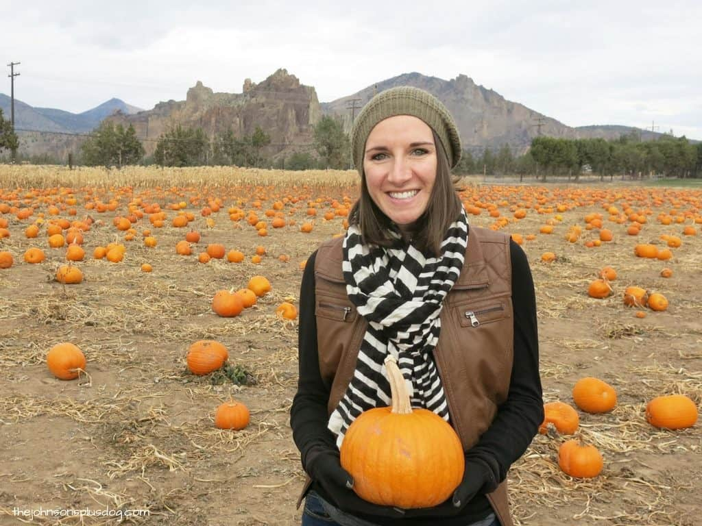 Girl at pumpkin patch holding pumpkin in front of belly to announce pregnancy