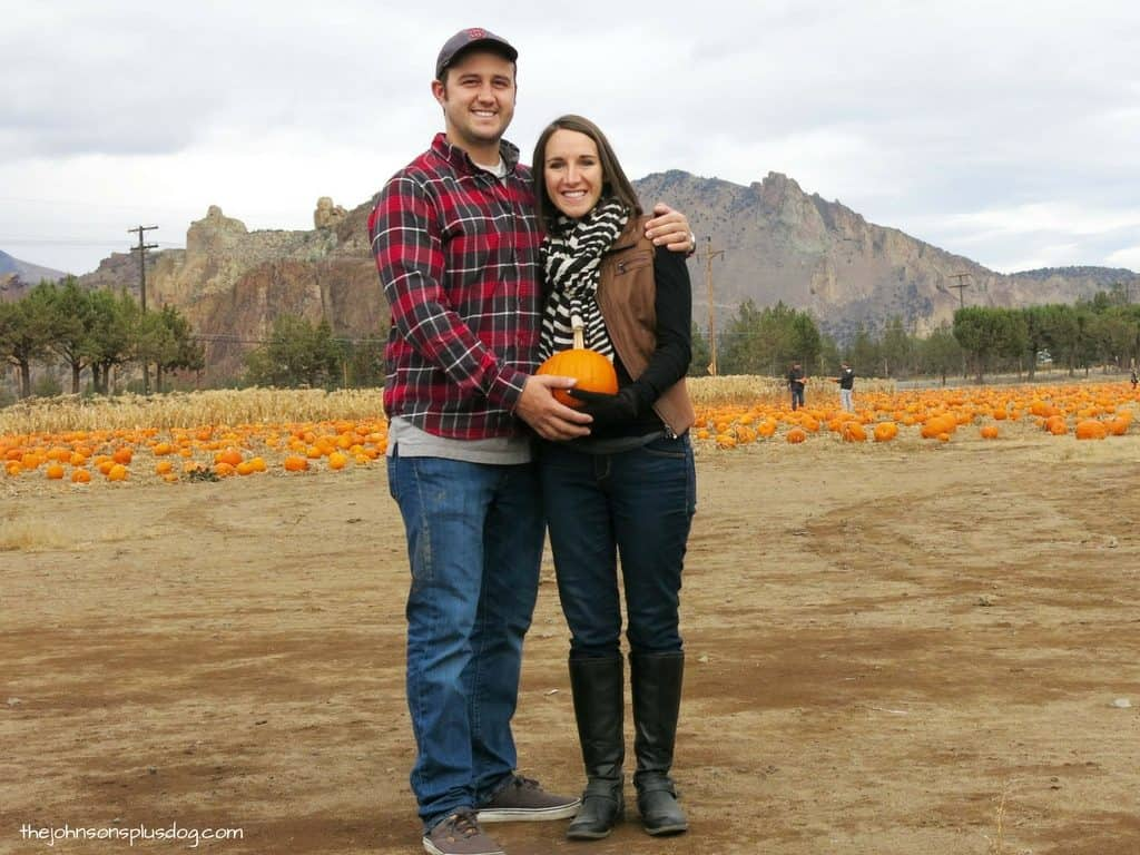Couple at pumpkin patch holding pumpkin in front of woman's belly for a cute Halloween pregnancy announcement