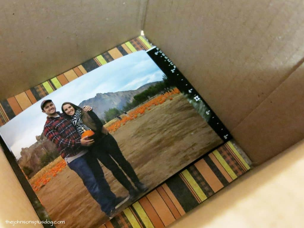 Halloween pregnancy announcement photos sitting at the bottom of a box lined with Halloween themes paper