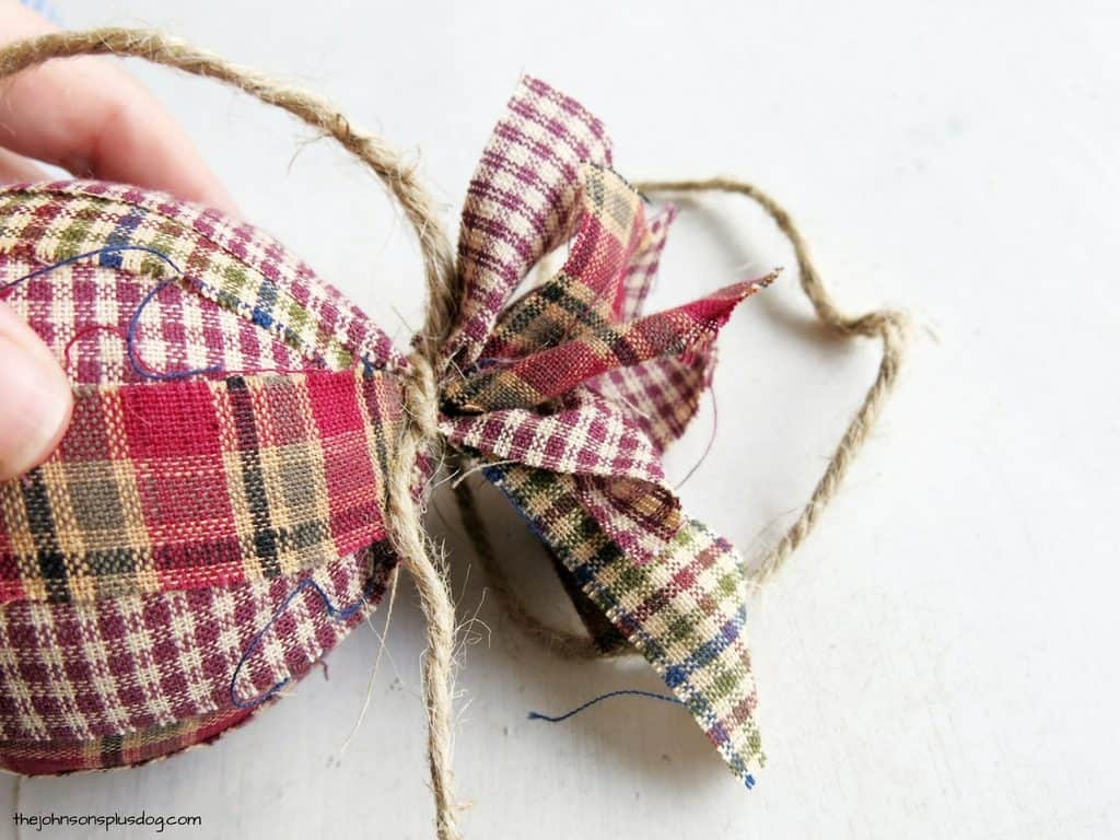 a homemade ornament covered in fabric with twine tying it off on the side