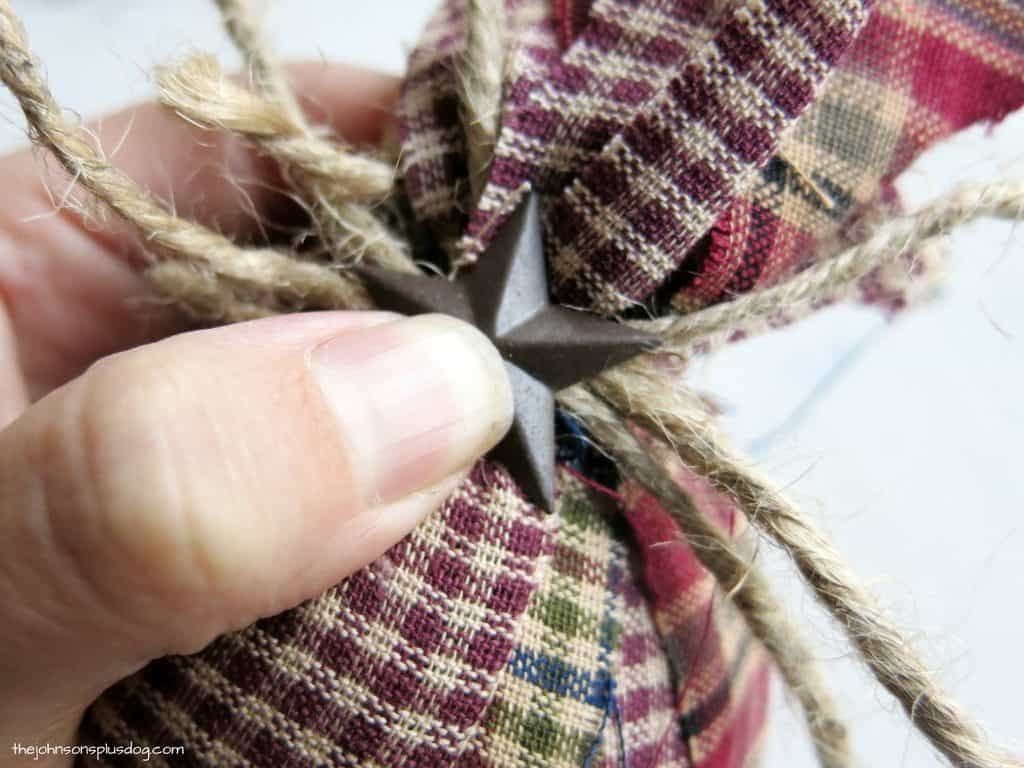 gluing a small star shaped piece of metal on to twine that's tied around a homemade ornament covered in fabric