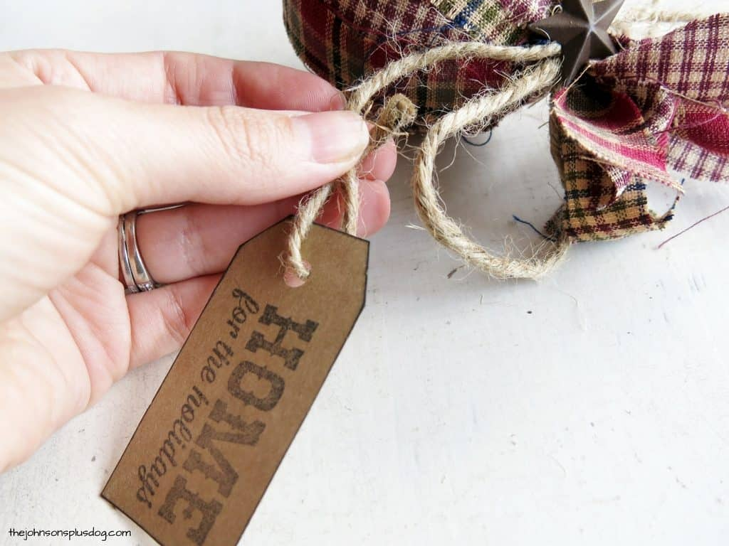 a hand tying a decorative tag to twine tied to a handmade ornament