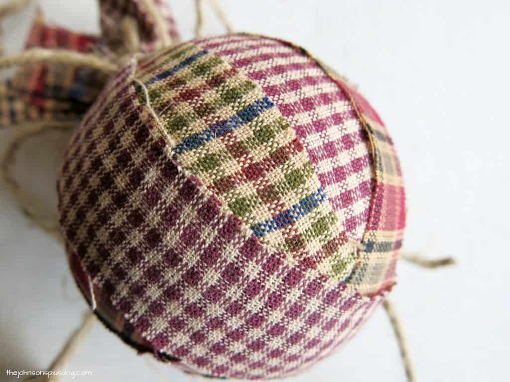 bottom view of the completed ornament, it is round and covered in fabric