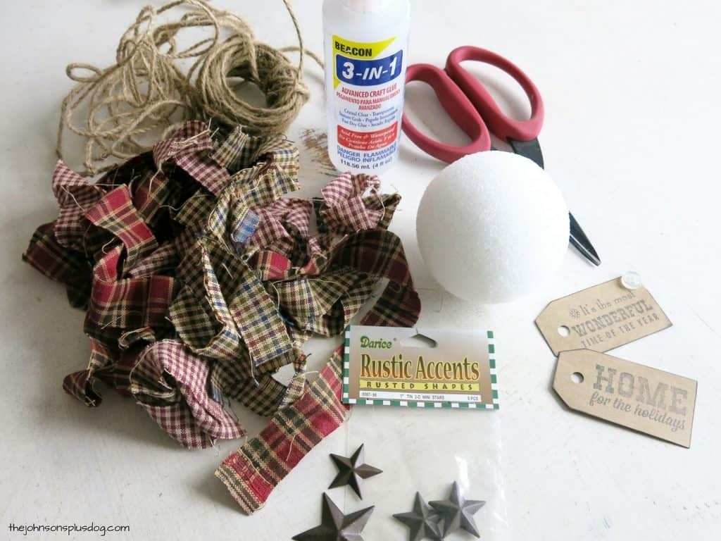 supplies are laid out on a white surface, there is fabric, twine, craft glue, scissors, a Styrofoam ball, some decorative tags, and small star shaped accents