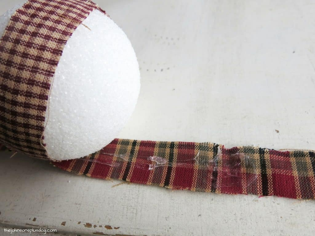 a styrofoam ball with a single fabric strip around it, and another laid underneath it with glue on the second fabric strip