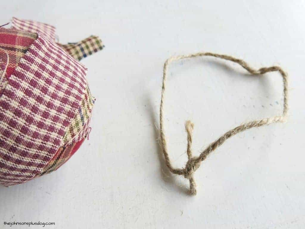 a fabric covered ball with a tied loop of twine next to it