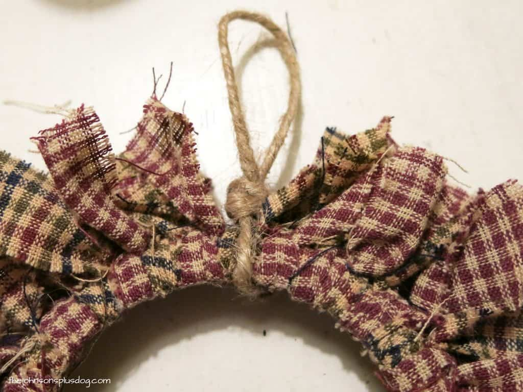 close up of twine tied around the edge of the wreath ornament creating a loop to hang the ornament