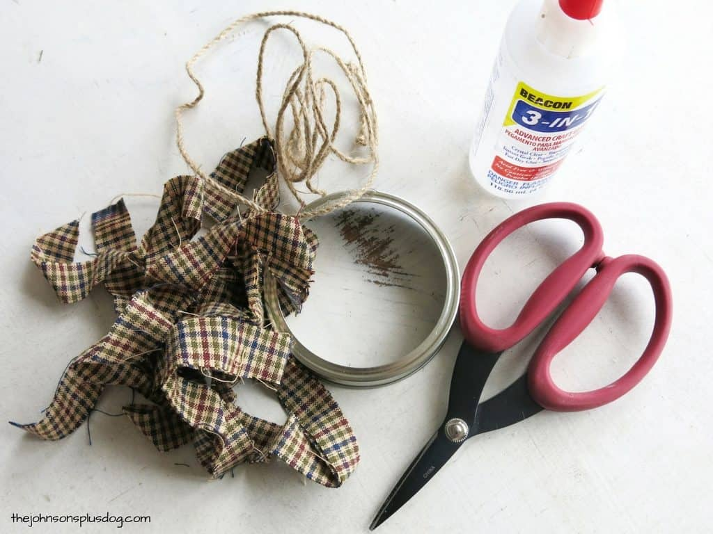 supplies on a white surface, supplies are a mason jar lid ring, scissors, fabric, twine, and craft glue