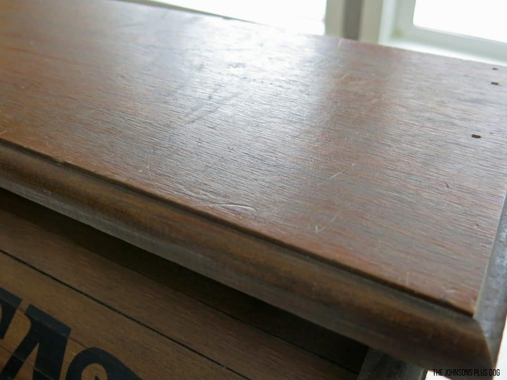 Top of vintage bread box showing wear and scratches in the wood