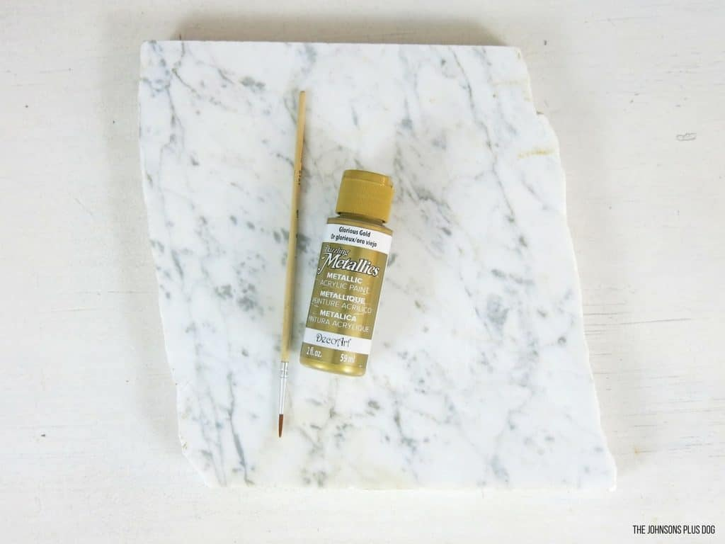 Small broken piece of carrara marble laying on white table with small paint brush and gold craft paint supplies laying on top of it