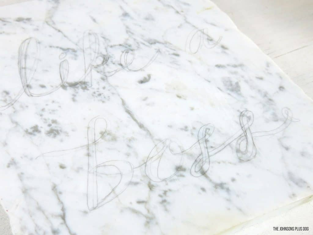 Close up shot of penciled cursive letters sketched out on top of marble before painting