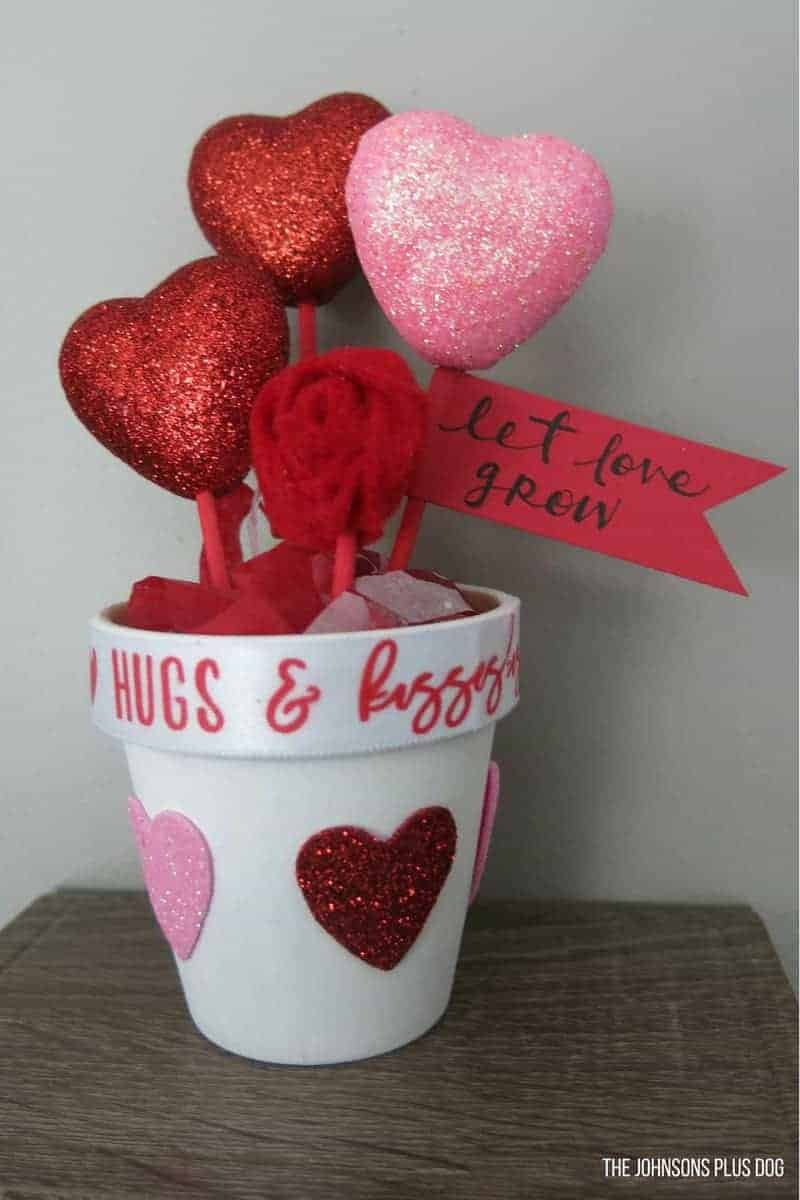 Valentine's Day Dollar Store Craft | DIY Valentine's Day Gift | Valentine's Day gift for teacher | Valentine's Day gift for nanny, Valentine's Day crafts, Valentine's Day decor, Valentines decorations, galentines party, Galentine's party ideas, potted hearts, hearts in a pot, pot of hearts, heart stems, Let Love Grow pot, Let Love Grow Dollar Store, Dollar Store Potted Plant, Dollar Store Pot of Hearts, Felt Rosette, Valentine's Day growing hearts, let love grow gift, DIY growing love, cheap DIY teacher gift