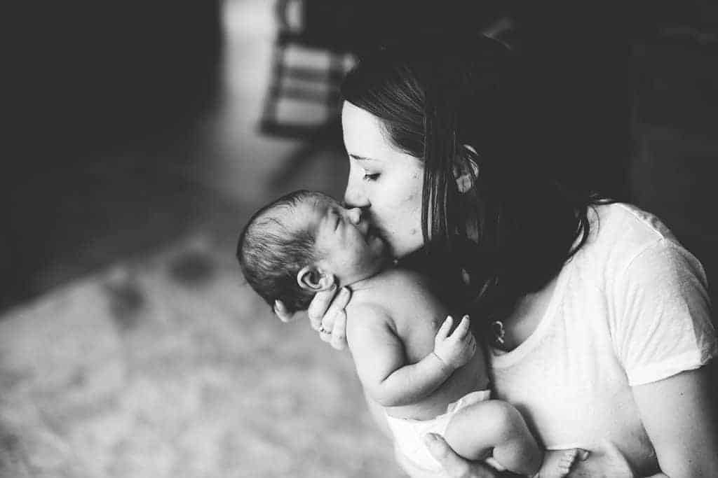 Black and white image of mother kissing newborn baby that is wearing a diaper and crying