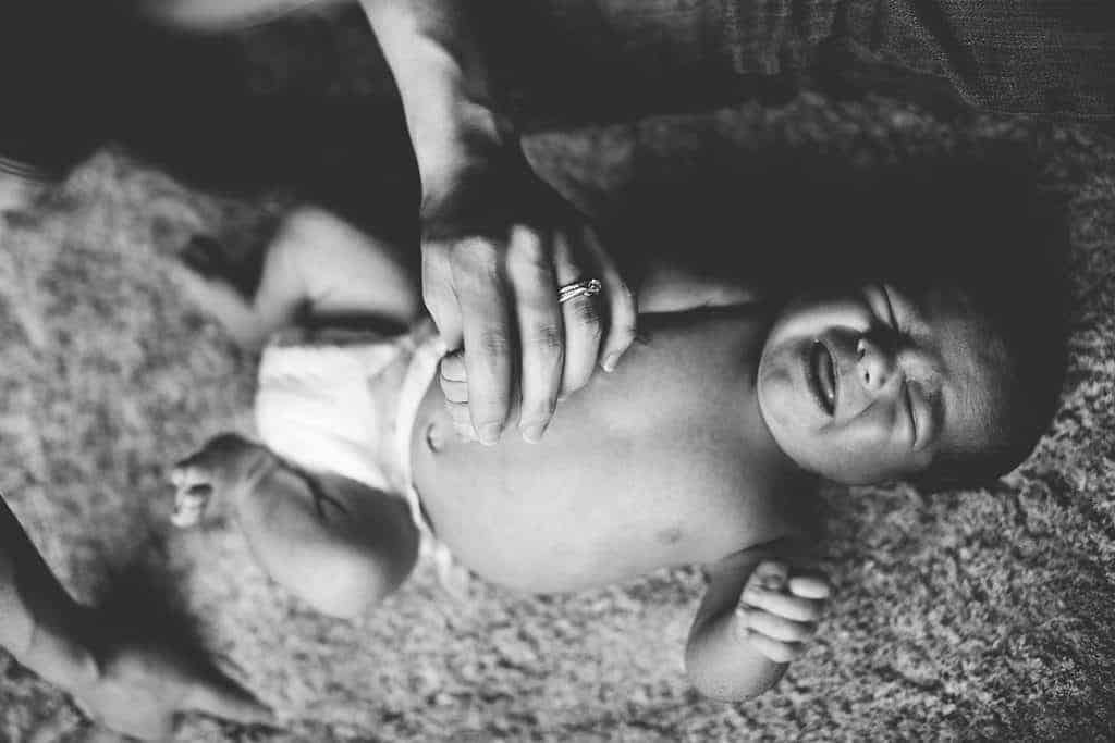 Black and white image of newborn baby crying on the floor wearing a diaper and mom is holding hand