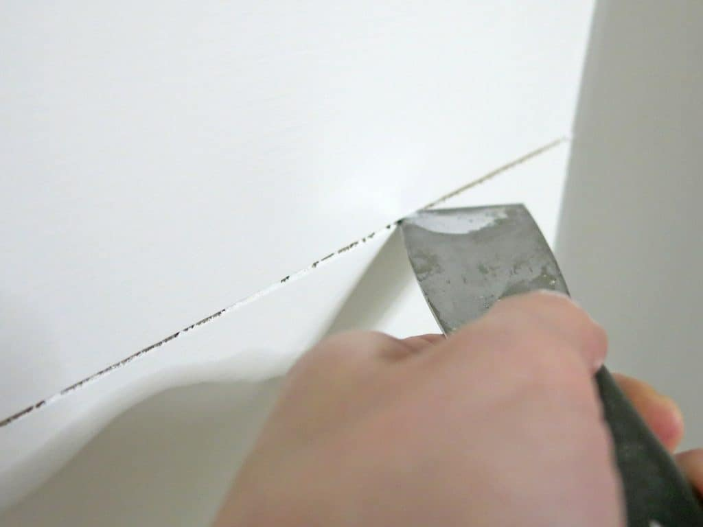 Hand running a putty knife through two painted planks with with drips to clean up the faux shiplap accent wall