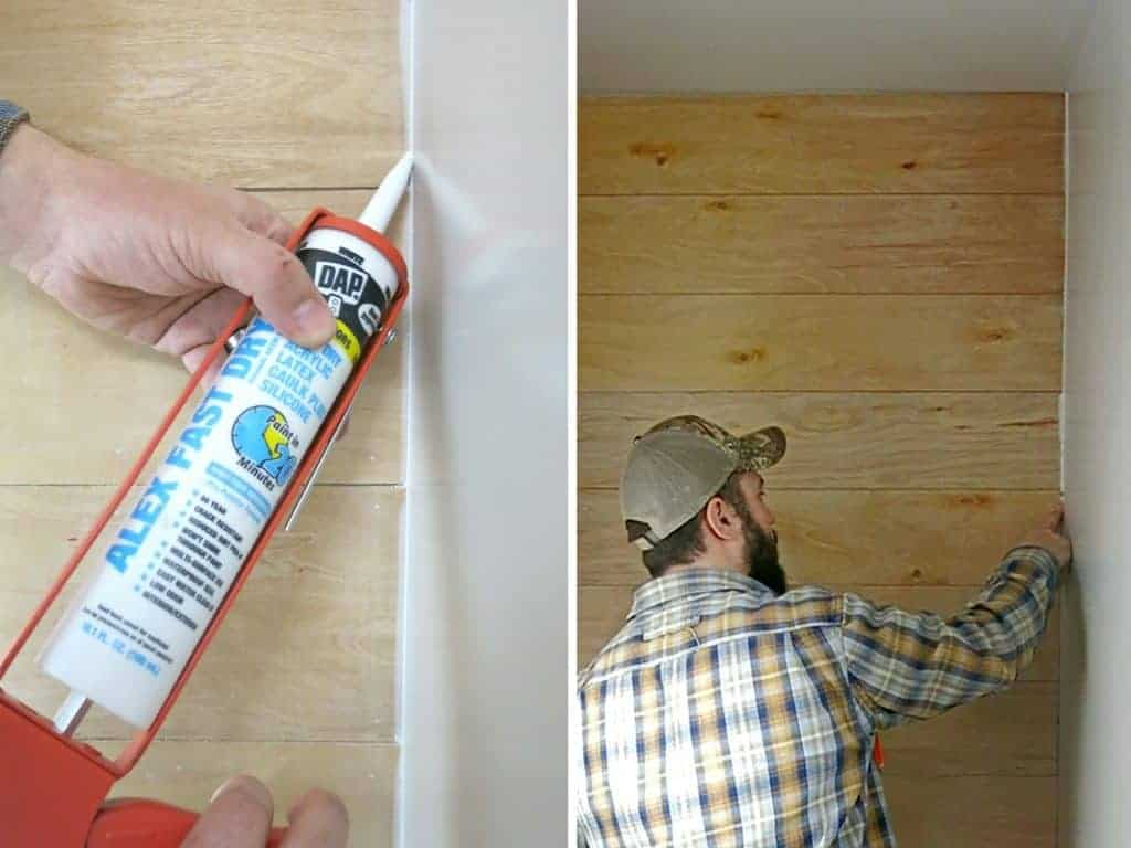 Man caulking edges of accent wall with wood planks