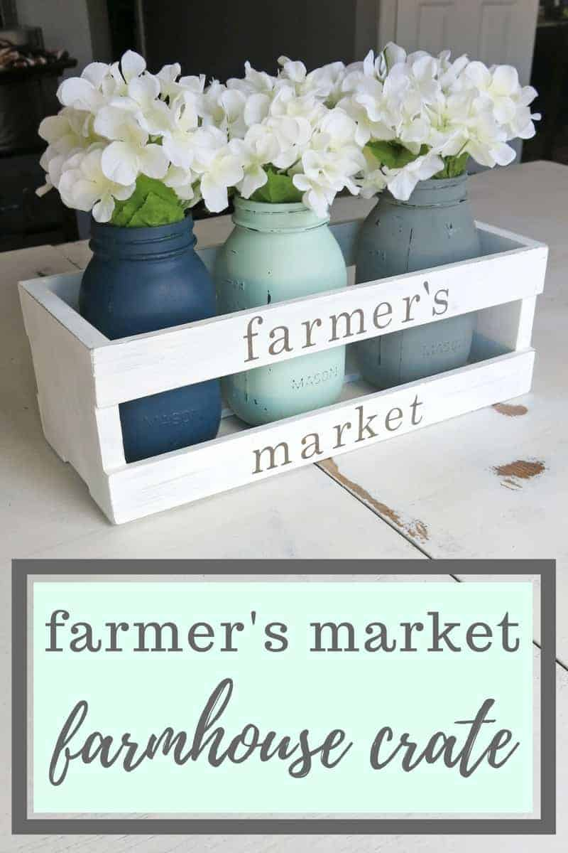 Farmer's Market Farmhouse Crate Centerpiece | Spring Farmhouse Wooden Crate | Farmhouse Style Crate | Fixer Upper Style Spring Decor | Painted Mason Jars with White Hydrangeas in Wood Crate | Wooden Crate with Farmer's Market on it | White distressed crate for mason jars and flowers | How to decorate for spring | Spring Decor | Brighten up your home with spring colors | Centerpiece for Spring table | Farmhouse centerpiece | Center piece for farmhouse tablescape | Decorate your table for Spring | Easter table decor