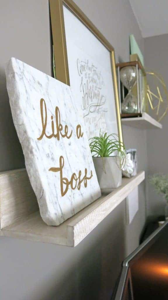 Side view of the Like a Boss paint on marble, gold printable in gold frame, concrete geometric planter and vintage hour glass on top of wall hang shelves